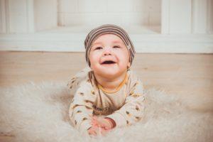 happy baby on rug on floor