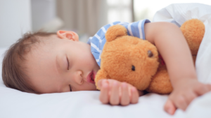 young boy with teddy bear sleeping soundly