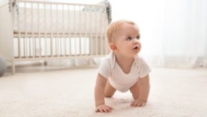 baby crawling, crib in background