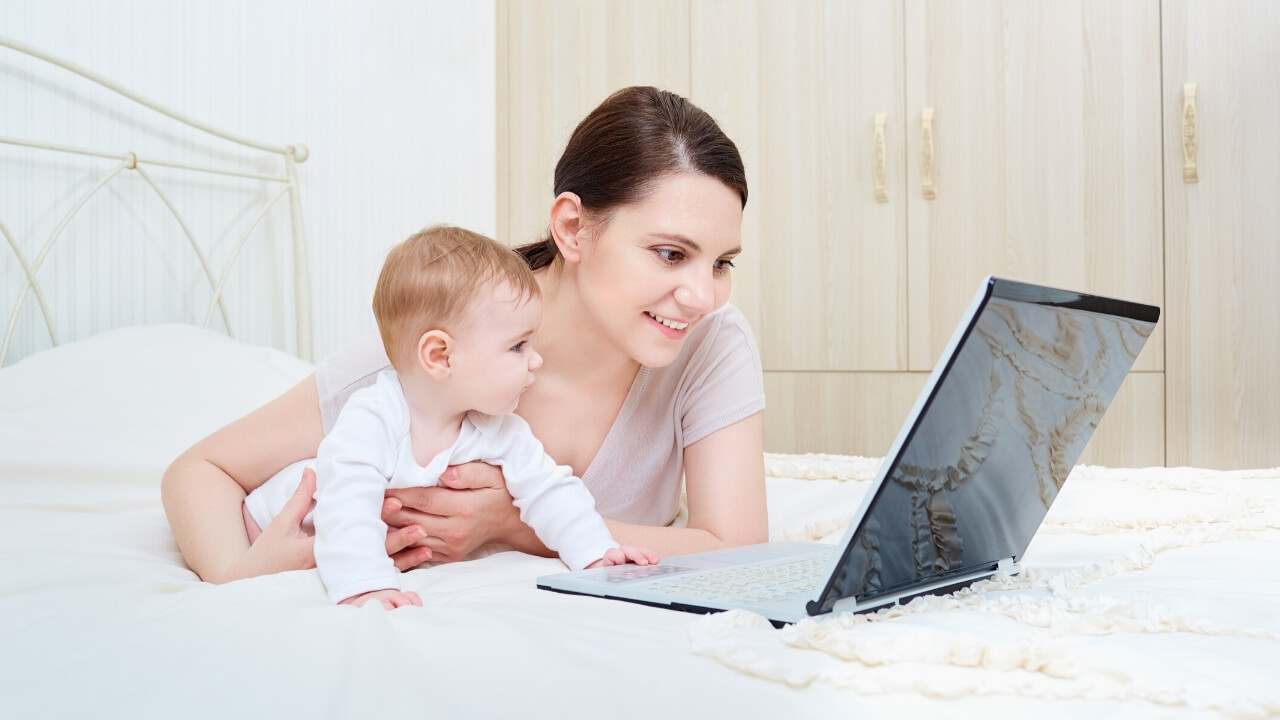 Mom and baby looking at computer - Tender Transitions